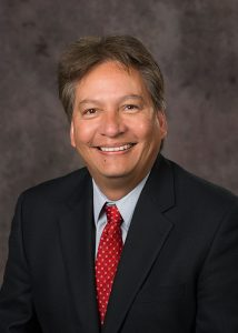 Headshot photo of Chris Cornelius smiling at the camera in a black suit with a red tie.