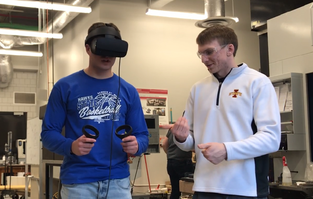 Student on left wears virtual reality goggles and simulates an environment, while the student on the right guides him.