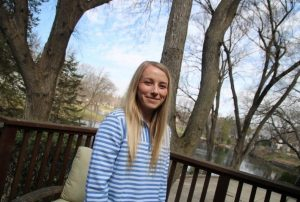 Photo of Emily Olson standing outside and smiling with trees in the background