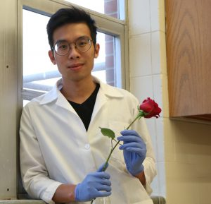 Photo of Andrew Martin in a lab coat and gloves, holding a red rose