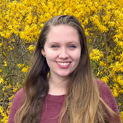 ME graduate student Emily Johnson poses in front of some yellow flowers.