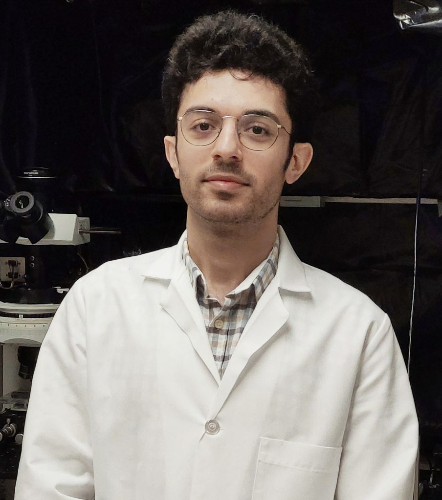 Shot of Hamidreza Zobeiri in a lab coat with lab equipment in the background