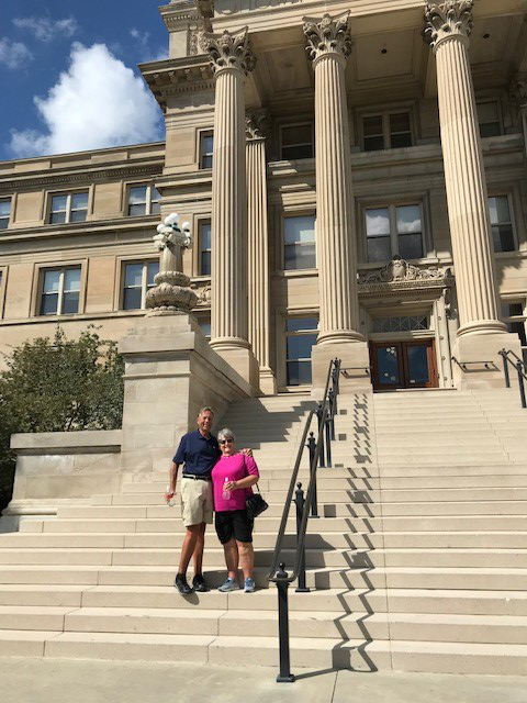 John and Sue pose on the steps with the massive columns of Beardshear Hall in the background