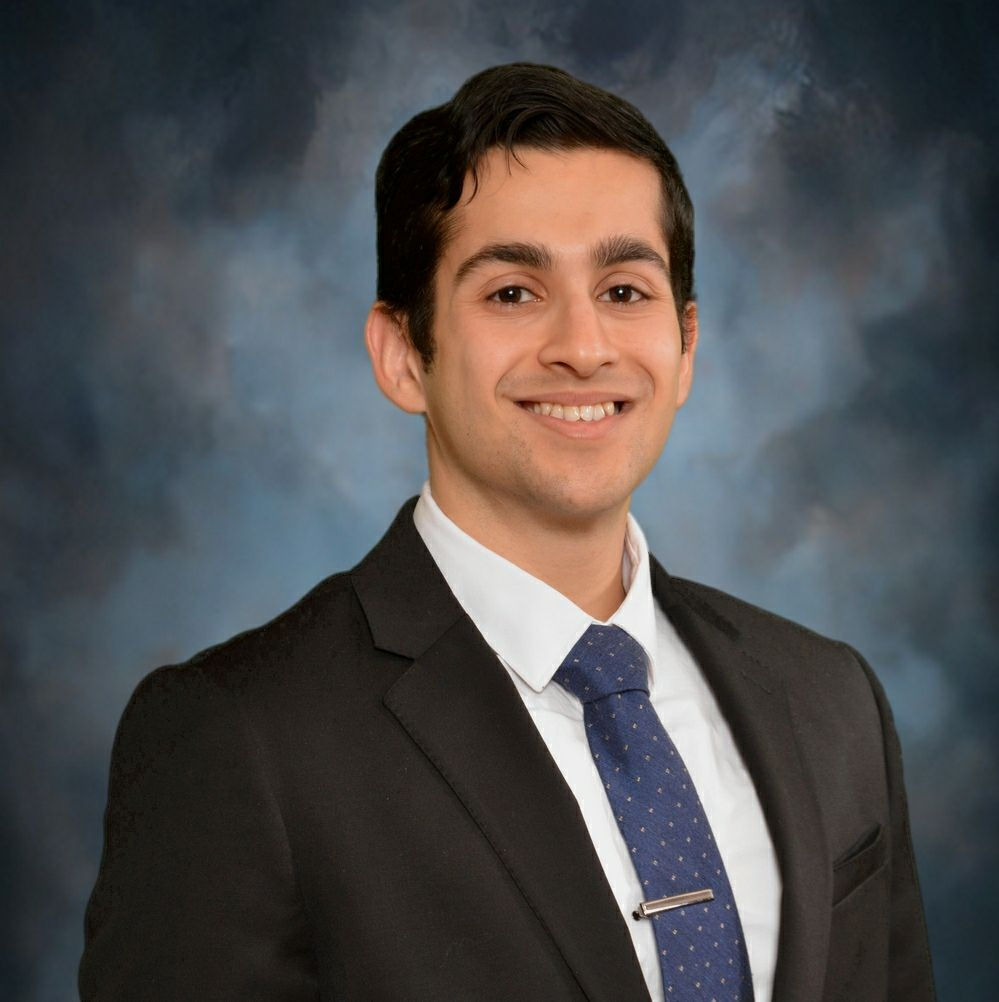 Mechanical engineering graduate student Murt Zohar smiles while wearing a black suit, a white collared shirt, and a blue neck tie.