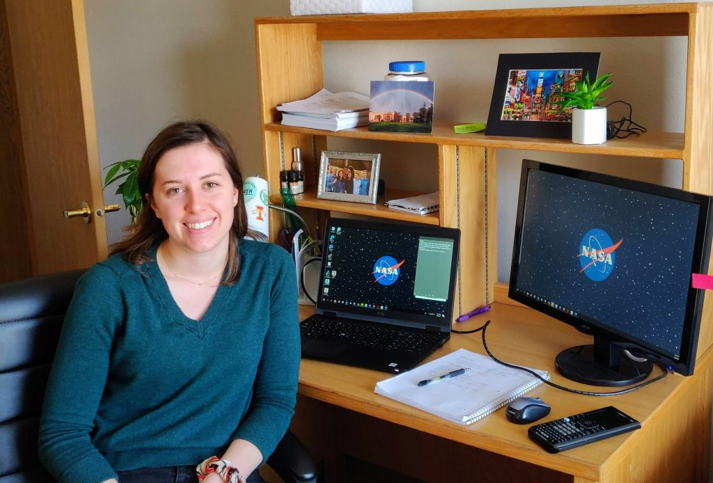 Mechanical engineering student Olivia Tyrrell smiles and poses in front of her desk. Both of her computer monitors have the NASA logo on them. A notepad and calculator are also seen in the shot.