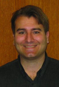 Mechanical engineering professor Michael Olsen smiles as he poses in front of a wooden door. He is wearing a black collared shirt.