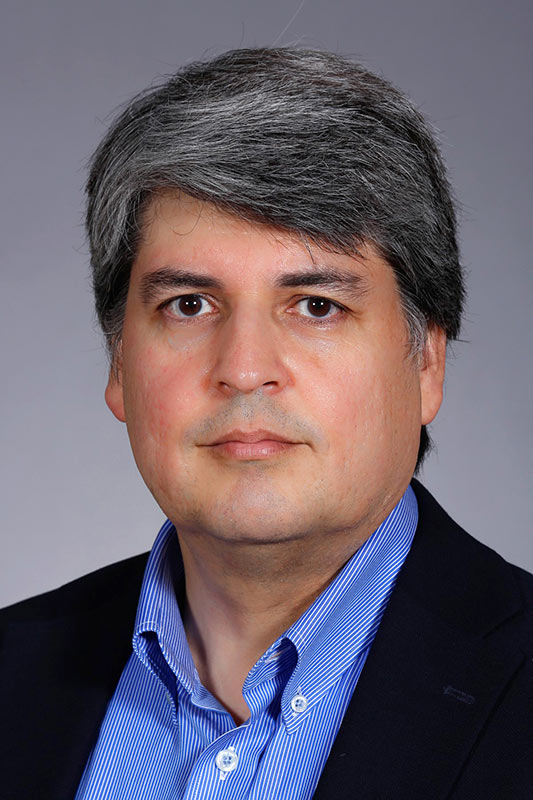 Dennis Vigil, professor of chemical and biological engineering, poses while wearing a blue collared shirt and a dark suit jacket.