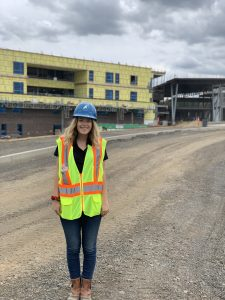 Student poses while wearing a hard hat and reflective vest on a construction work site.