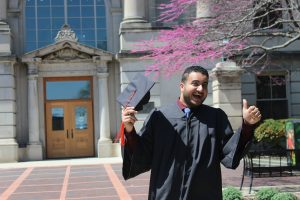 A man in a graduation gown smiles and gives a thumbs up. He's holding his graduation cap. In the background is Marston Hall, a bedroom limestone building on the Iowa State University campus.