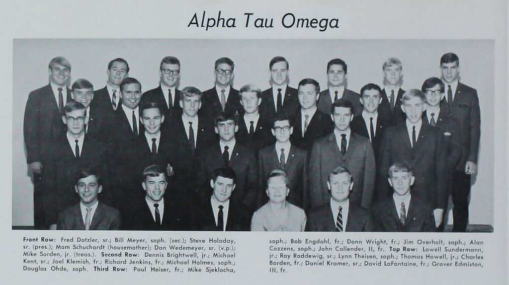 A black and white photo of brother from Alpha Tau Omega social fraternity. All of the brothers are wearing suits and ties, and most are smiling. The housemother - Mom Schuchardt - is the only female in the shot.