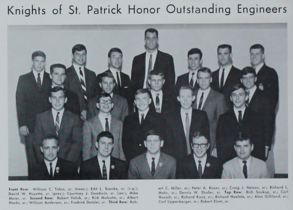 A black and white photo of men involved n the Knights of St. Patrick honorary society. All of the men in the shot are wearing suits and tie, and most of them are smiling at the camera.