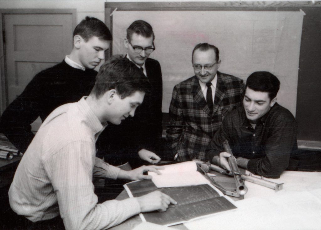 A black and white photo from the 1970s of four students and a professor. It appears the group is creating a scene from a plant design course.