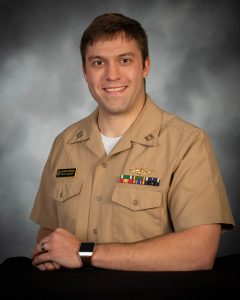 Ben McFarland poses in his military uniform. The uniform is tan and Ben wears several pins above his left breast pocket.