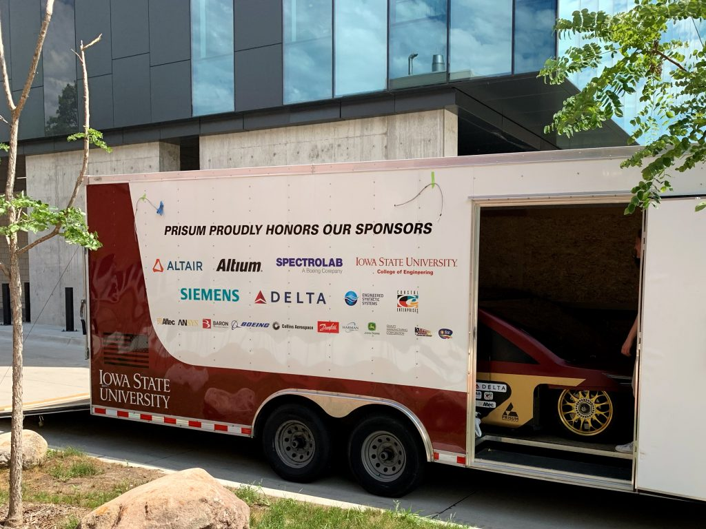 A shot of Team's PrISUm's trailer with the solar car on the inside. The trailer bears stickers for the team's sponsors.