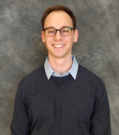 Mechanical engineering graduate student Adam Thelen smiles while wearing a light blue collared shirt and a grey sweater.