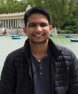 Mechanical engineering graduate student Ankush Mishra poses while wearing a black jacket and a blue collared shirt. Boats on water can be seen in the background.