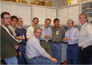 Cornelius stands with a group of scientists, smiling