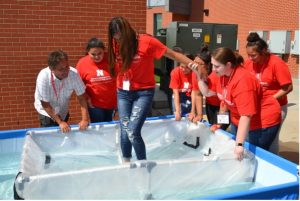 Cornelius stands with a group of students at a summer camp, and they are testing boat floatation