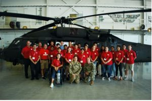 Cornelius surrounded by high school summer camp kids in front of a National Guard helicopter