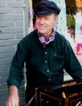 Color photo of David Wilder, smiling and wearing a hat and scarf around his neck