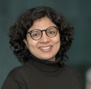 Headshot photo of Shana Moothedath smiling and wearing glasses