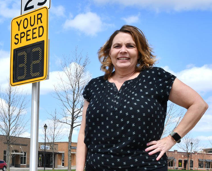 Shauna Hallmarks stands in front of a street sign