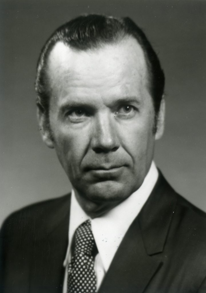 Black and white headshot photo of David Wilder in a suit and tie