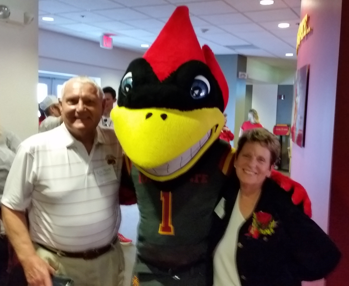 Alums Joyce and Turk Therkildsen pose with Cy the Cardinal, the mason for the Iowa State University Cyclones.