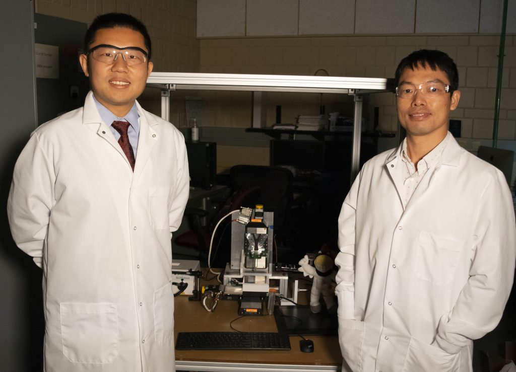 Materials science and engineering assistant professor Shan Jiang and industrial and manufacturing systems engineering assistant professor Hantang Qin pose inside a laboratory on the Iowa State University campus. A 3D printer can be seen in the background of the shot.