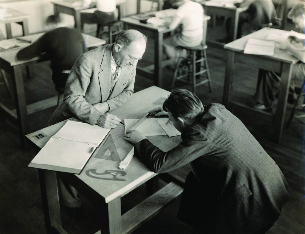 A black and white photo of an industrial engineering professor working with a student in a drafting class, sometimes in the 1930s.