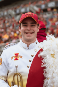 Jacob Schmieder smiles while dressed in his marching band uniform and holding his trumpet.