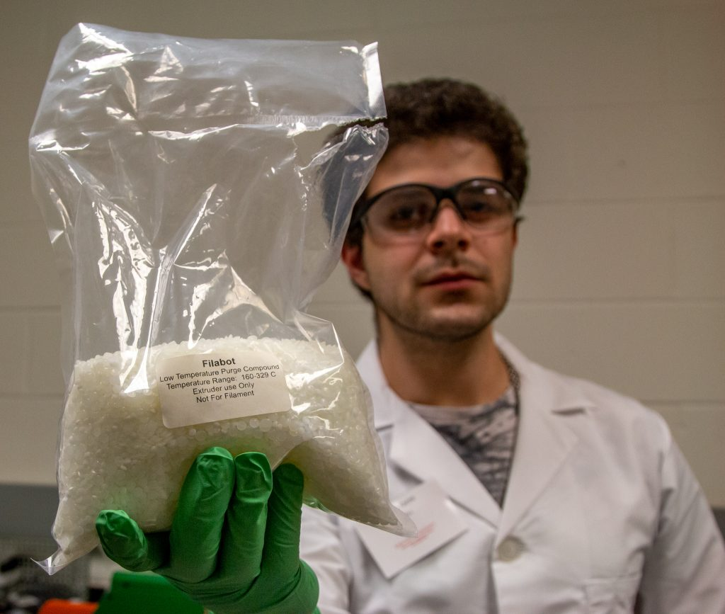 Ayman Karmi holds up a bag of plastic materials produced by the Filabot Extruder.