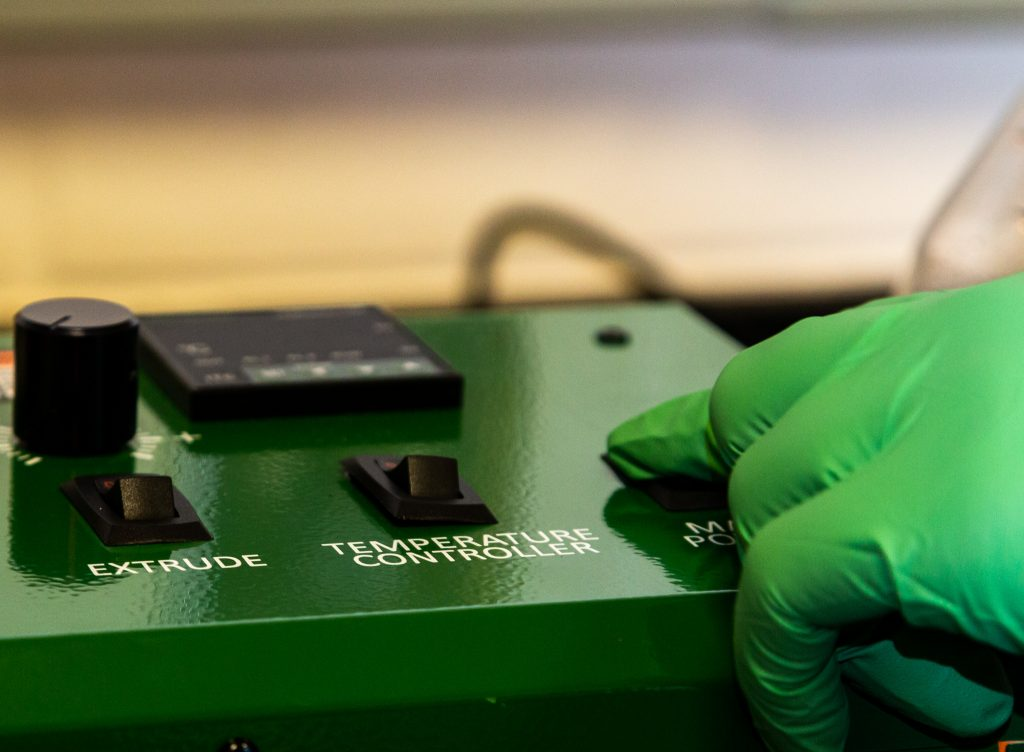 Ayman Karmi clicks a button on a Filabot Extruder machine in the REFORM lab.