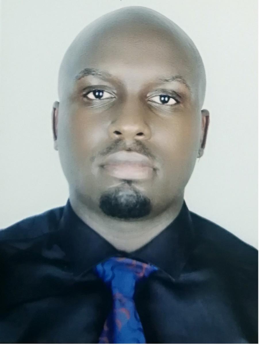 Headshot of Iowa State University alum Denis Bbosa. He is wearing a black shirt and a blue tie.