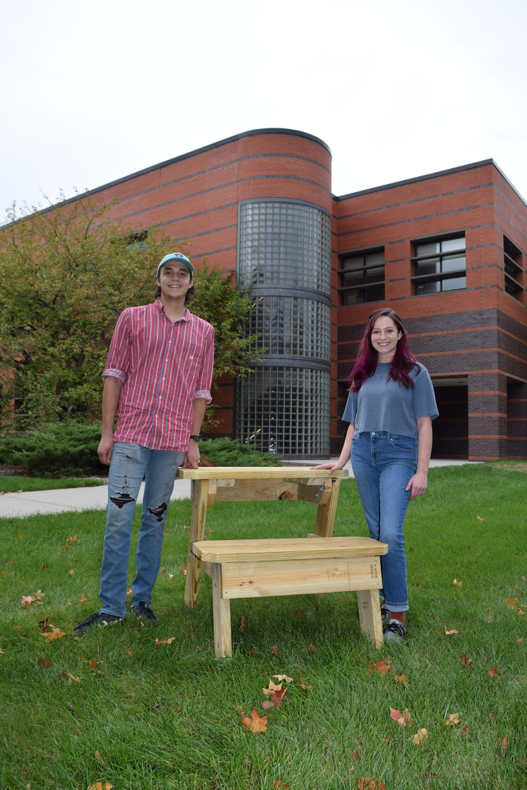 Two students stand outside of Black Engineering Building next to a desk they helped to design and fabricate.